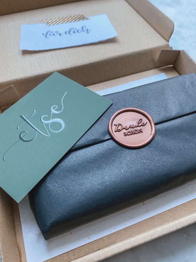 Paket einer Bestellung, offen mit Visitenkarte, Seidenpapier und Stempel